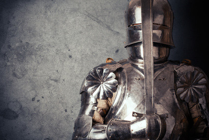 Medieval knight fully encased in armour holding a sword