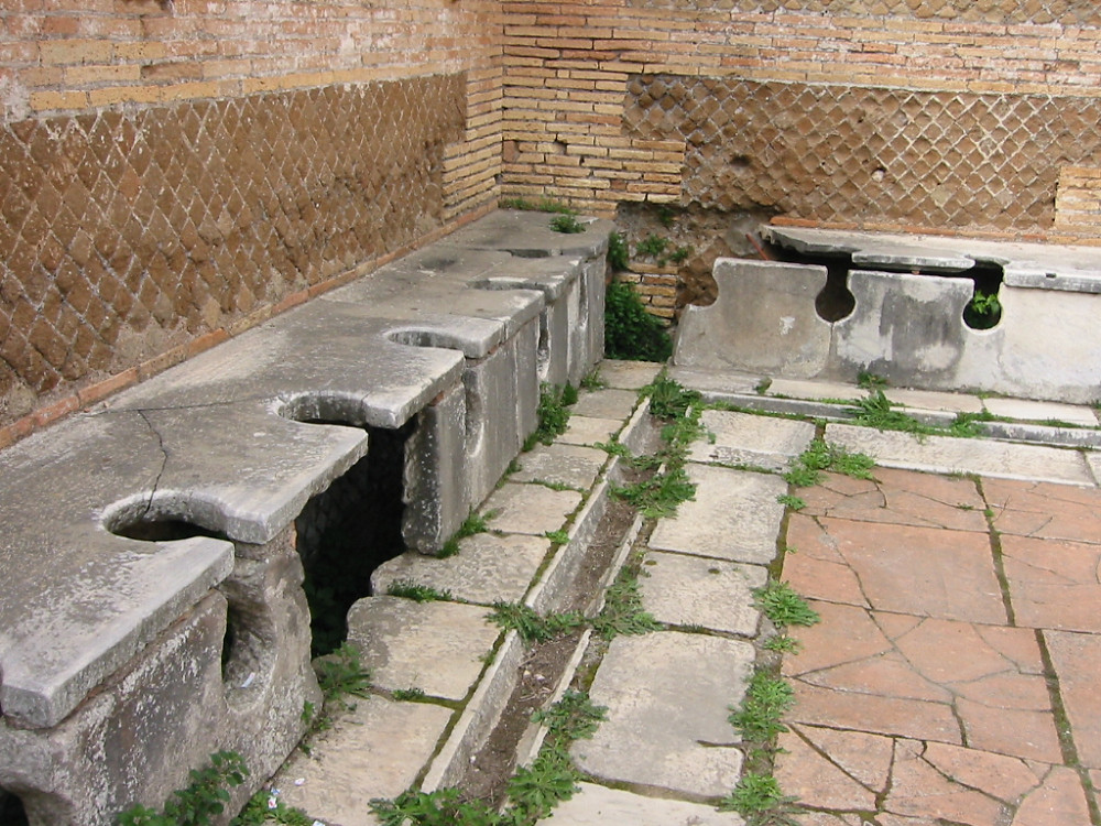 Ostia Roman trench Toilets By Fubar Obfusco - en.wiki, Public Domain, https://commons.wikimedia.org/w/index.php?curid=287299