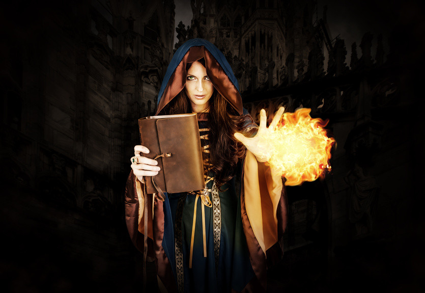 Cloaked and hooded woman holding a book in one hand and an orb of fire in the other