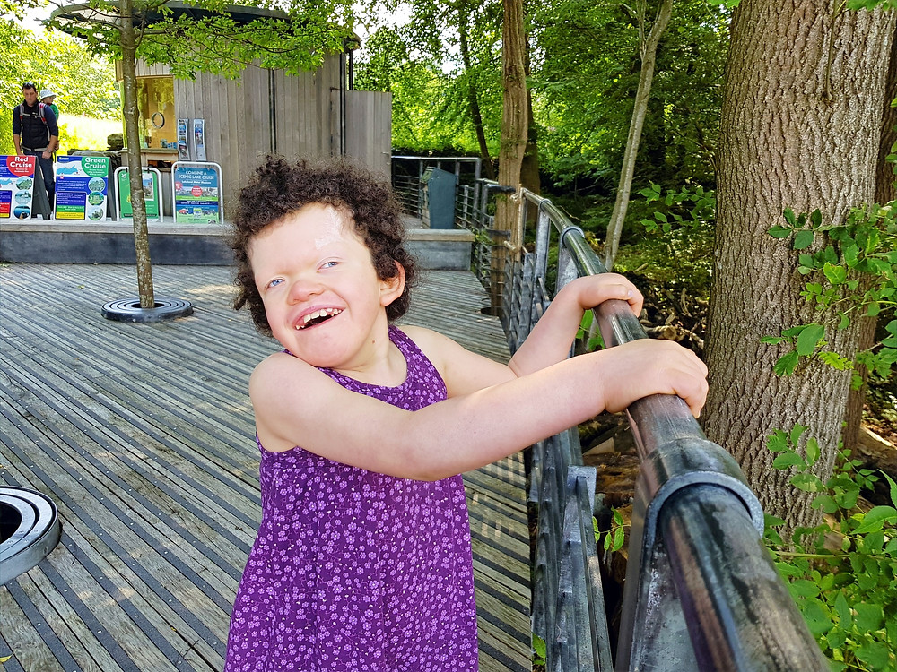 Carys , smiling in a purple dress, standing and holding onto a handrail beneath some trees