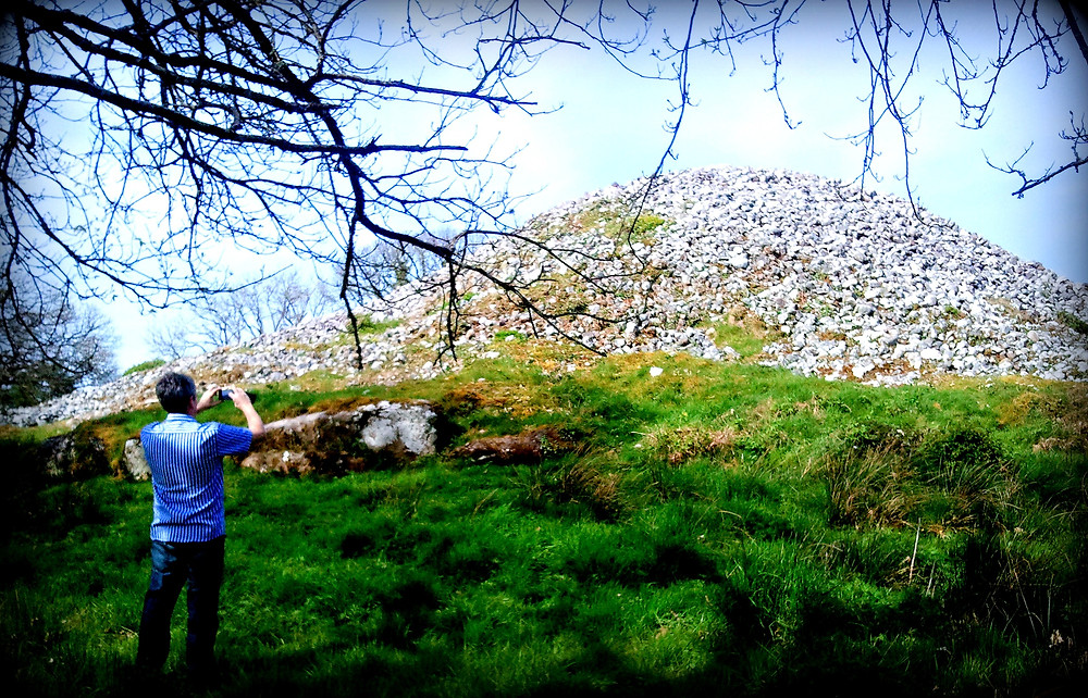 Huge stone cairn, grassy foreground, man taking photo