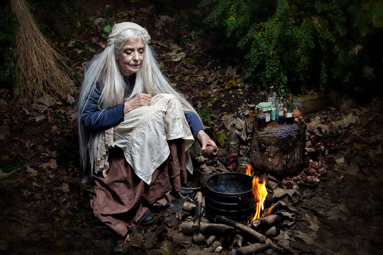 Grey-haired old woman sits alone at a campfire in a dark forest