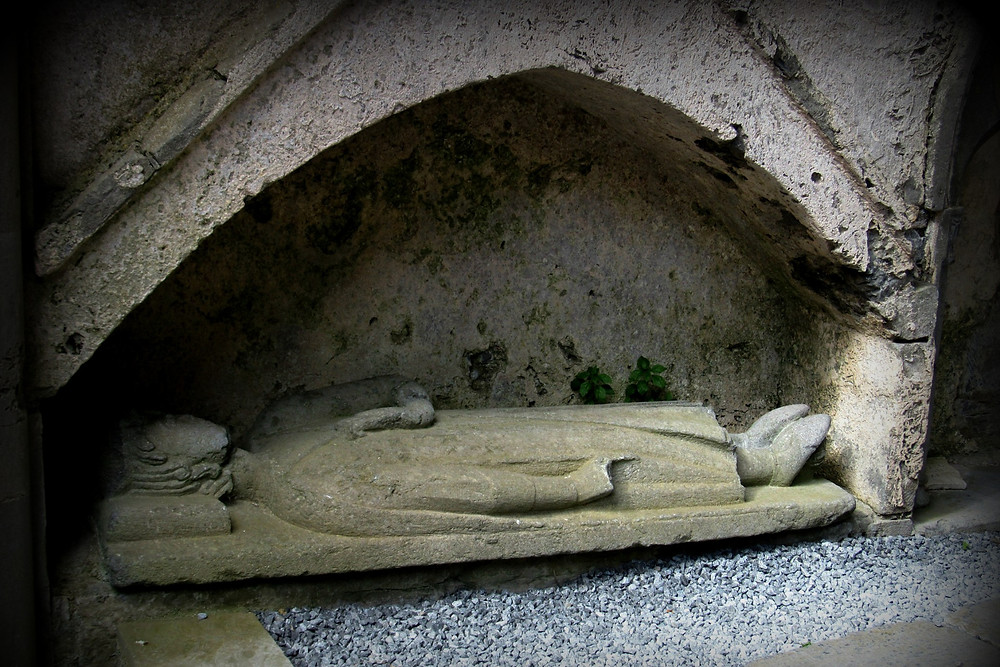 Stone effigy of man lying down in niche at Corcomroe Abbey.