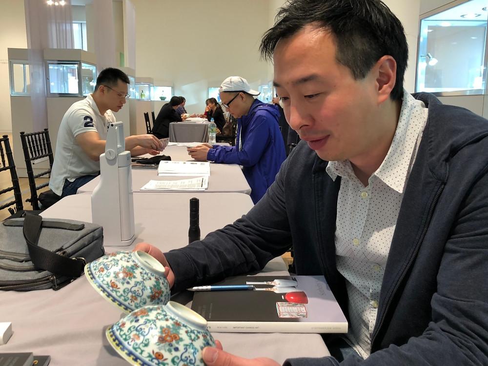 Me Examining Pair of Doucai Bowls, at Sotheby's