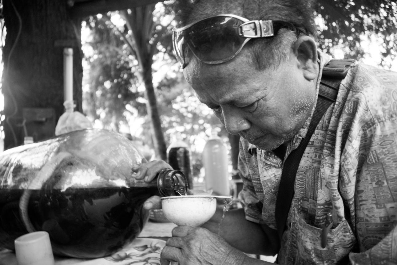 Laos, old man preparing local spirit