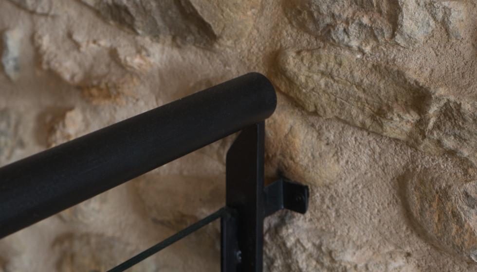 Detall barana amb paret de pedra