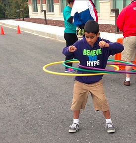 child with hula hoop outside on road