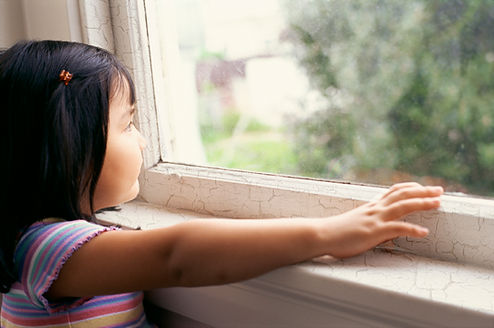 Female Asian child looking out old window to the outside