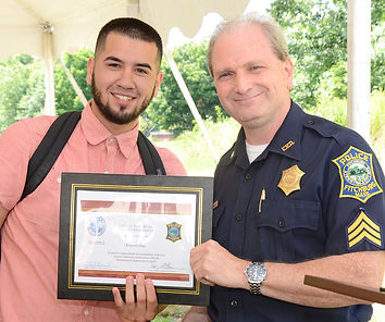 Teen, young adult receiving award from police official