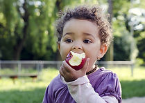 curly hair toddler eating apple