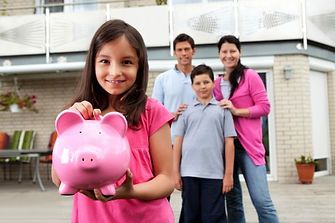 young girl holding piggy bank, family watches