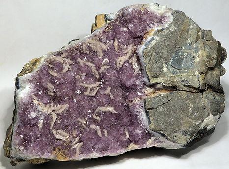 Густо- и светлоокрашенные аметисты Ольского плато в крупных жеодах (иногда с поздним кальцитом) и центральных полостях халцедон-кварцевых агатов