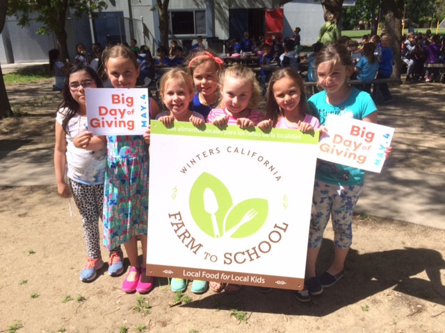 """Left to right:  Waggoner first-graders, Arely Figueroa, Ava Estepa, Sylvia Mattson, Jayde Mathias, Jillian Ries, Natalie Morris, Emma Glaudel share their enthusiasm for Winters Farm to School participating in this year's Big Day of Giving ... supporting """"local foods for local kids."""""""