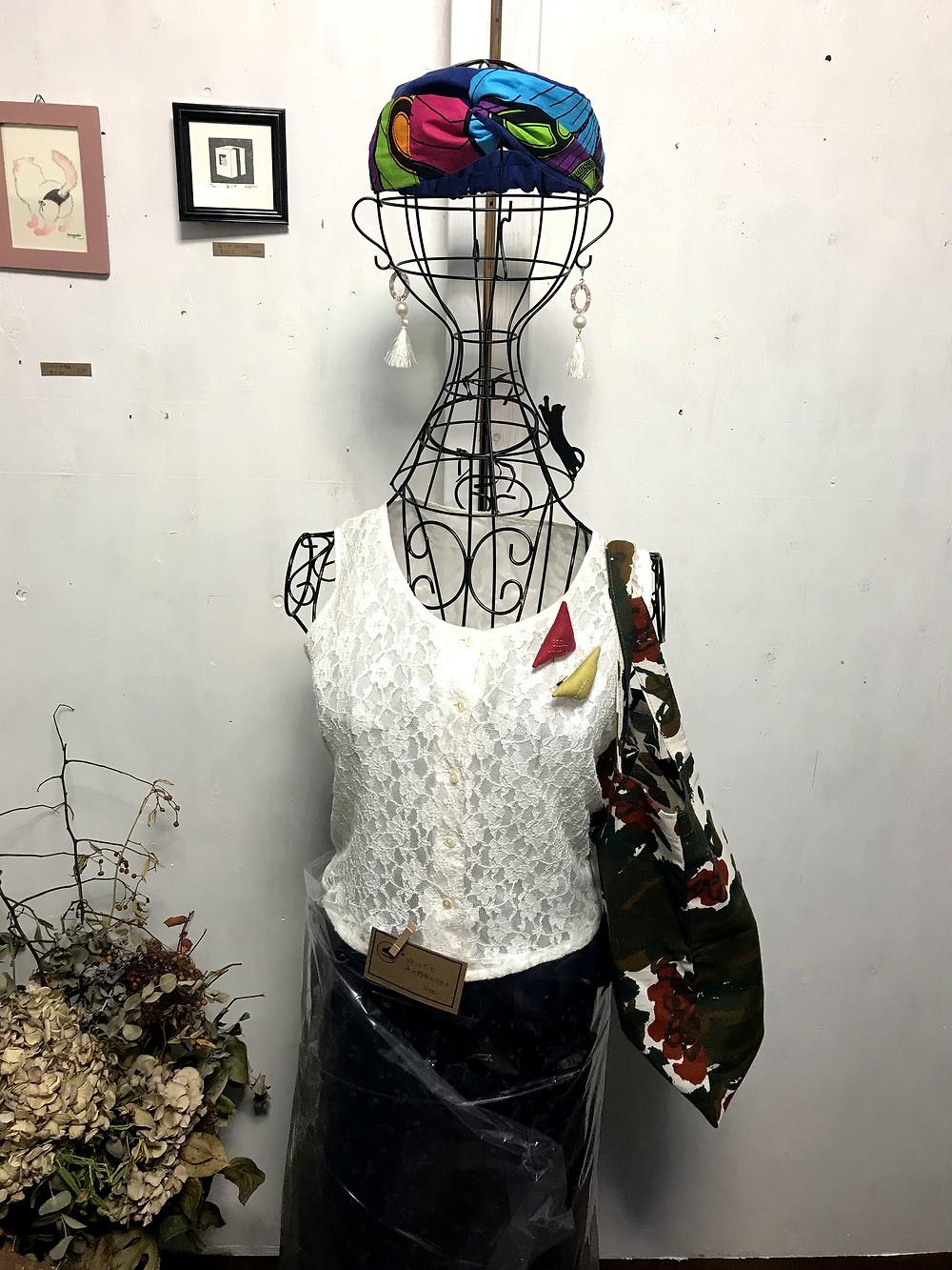 ファストファッションのブラウスとガーゼの振れ明日スカートという地味な装いにぱっと目を引くアフリカ布のターバンを合わせて。胸のリネンのぬいぐるみブローチはいろいろ使えます。