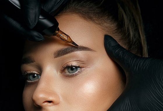 Beautician hand doing brow permanent makeup on an attractive female face_.jpg