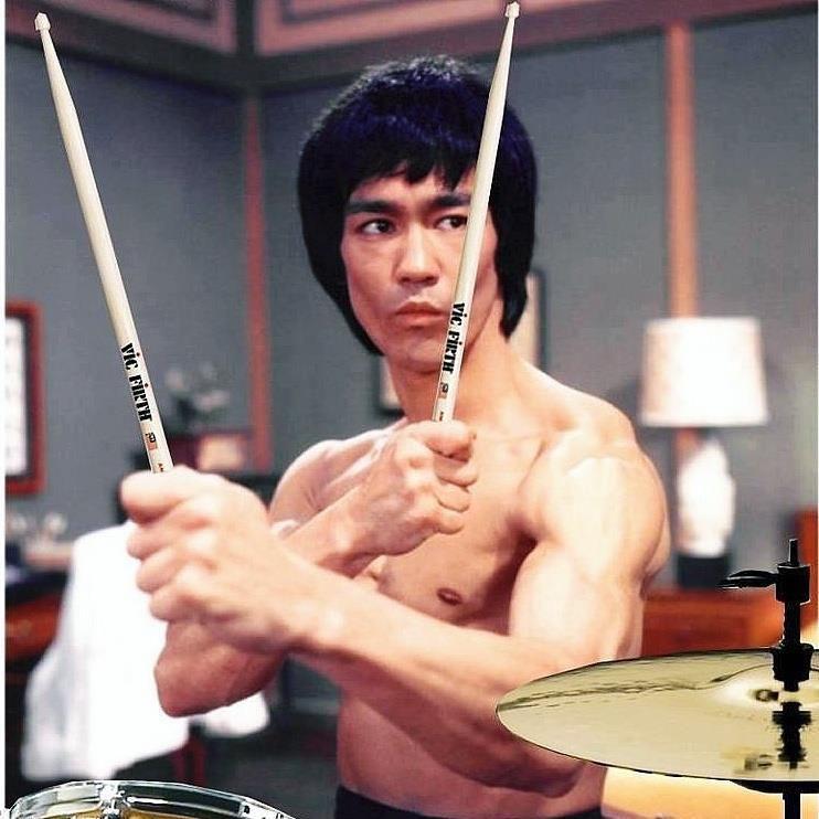 Bruce Lee holding Vic Firth Drum Sticks