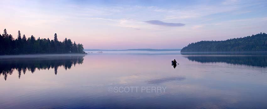 At dawn a canoeist paddles on Allagash Lake in northern Maine.