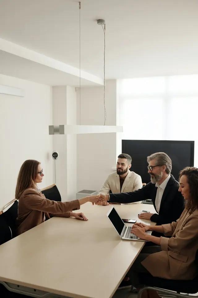 Una mujer cerrando un trato con ejecutivos