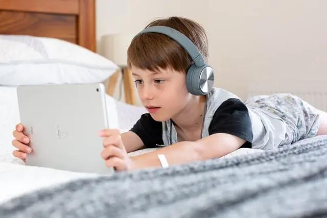 Niño con audífonos mirando una tablet