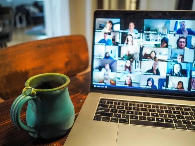 Una laptop en la cual vemos una videollamada con varios participantes. Hay una taza azul junto a la laptop