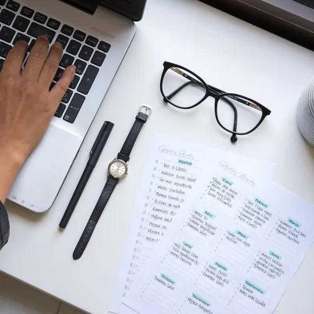 Una mano escribiendo en una laptop junto a objetos de oficina