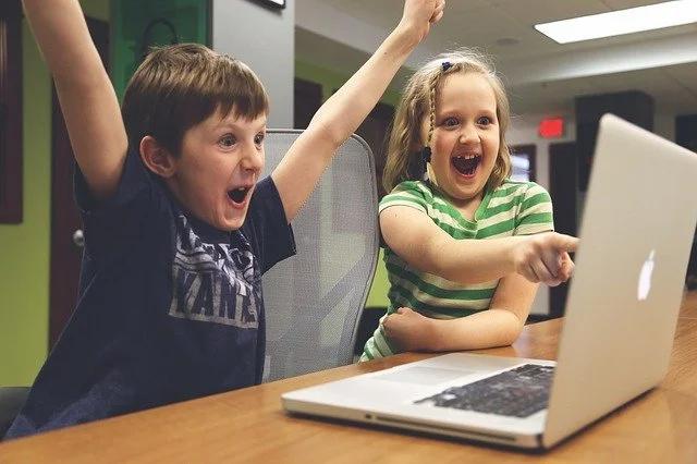 Una niña sorprendida señala la pantalla de una laptop mientras un niño celebra emocionado