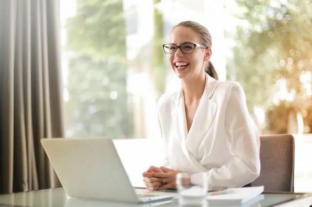 Mujer sonriente sentada en un escritorio