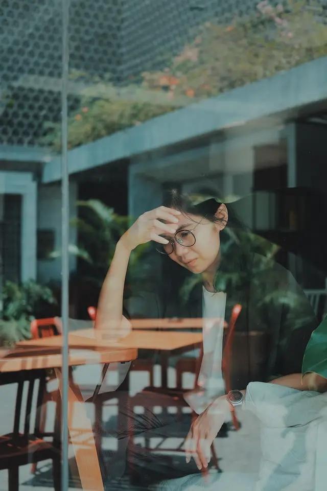 Muchacha triste sentada en una mesa y vista a través de una ventana