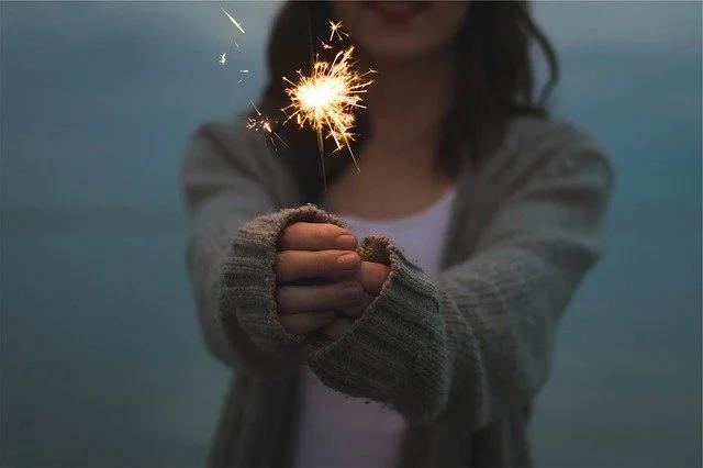 Una chica con una luz de bengala encendida