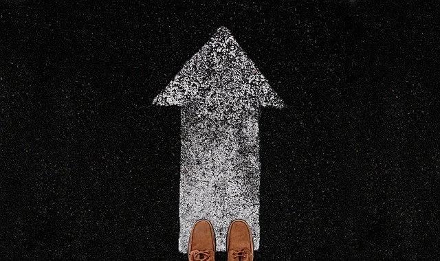 Un par de pies parados sobre una flecha pintada en el asfalto