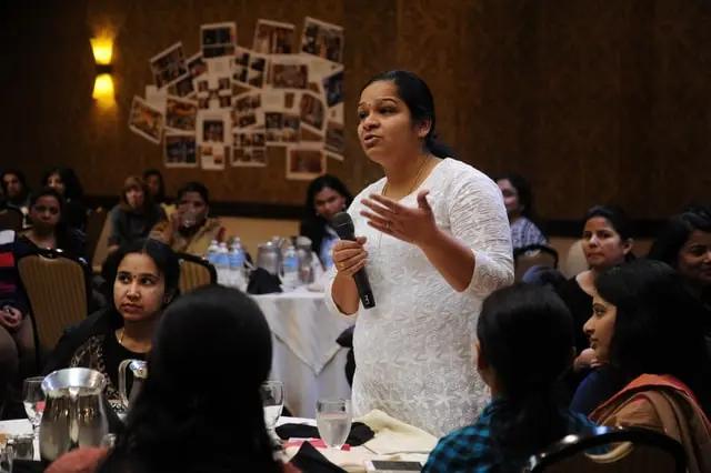 En una reunión, una mujer toma el micrófono para hablar