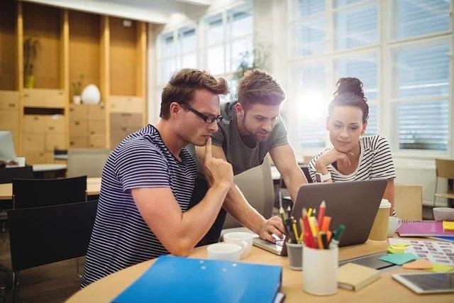 Tres jóvenes miran con atención la pantalla de una laptop