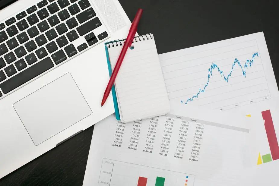 Hojas con gráficos estadísticos junto a una laptop