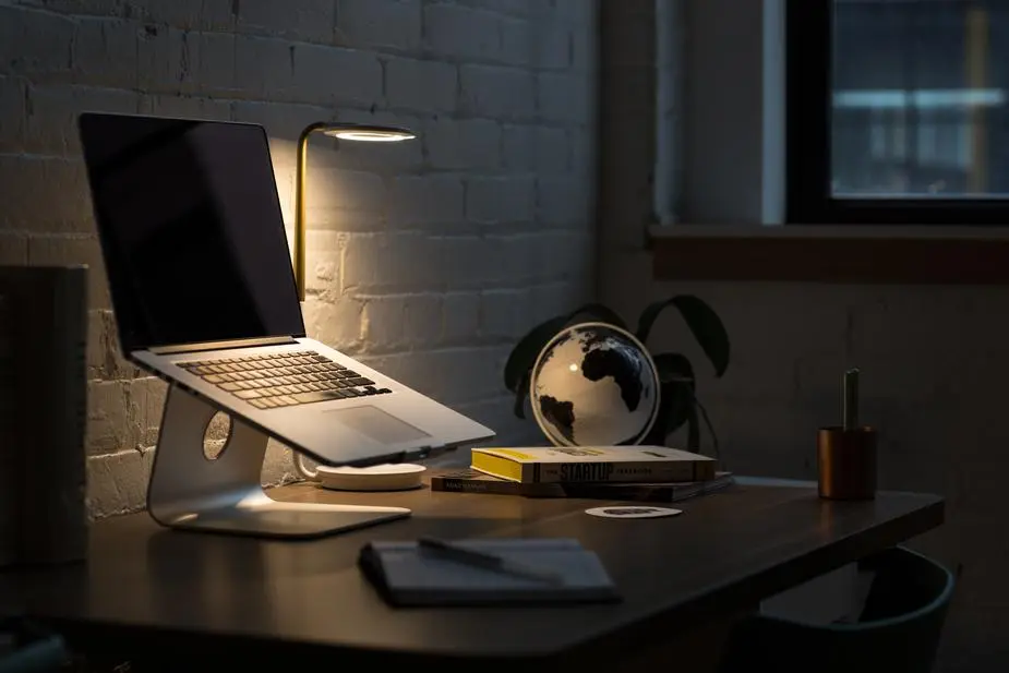 Laptop sobre escritoro con lámpara