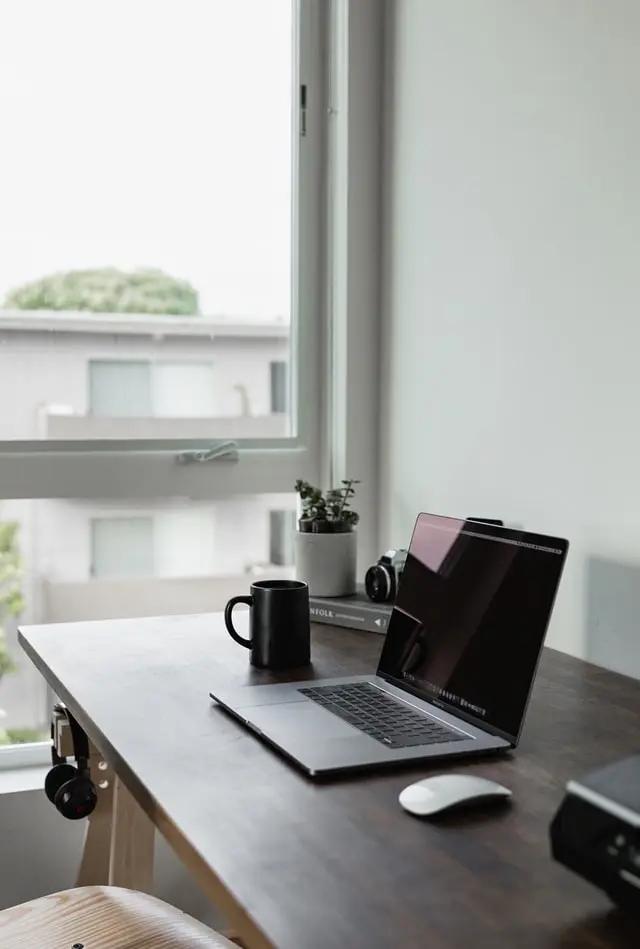 Escritorio con laptop frente a una ventana