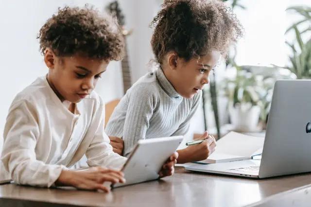 Niños frente a laptop y tablet