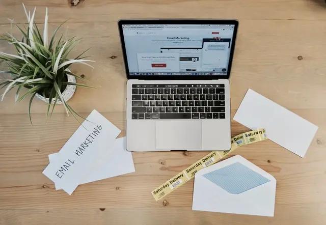 """Una laptop sobre una mesa, junto a ella vemos un sobre y un papel que tiene escrita la palabra """"Email marketing"""""""