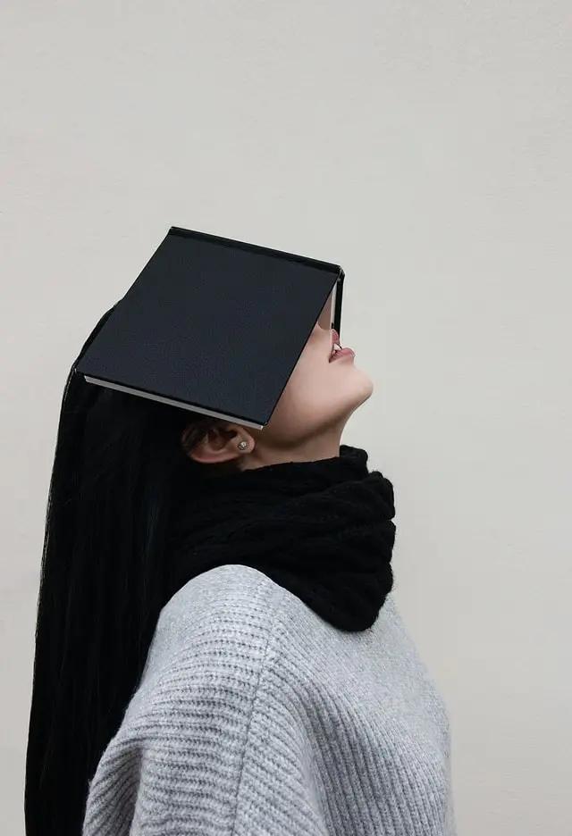 Alumna con libro tapándole la cara