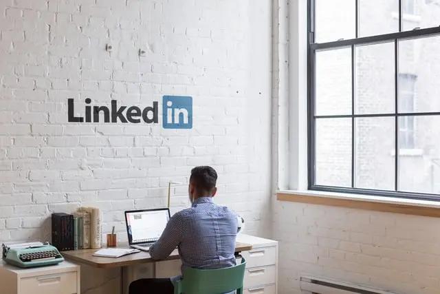 Hombre trabajando en un espacio de trabajo que tiene dibujado el logotipo de LinkedIn en la pared