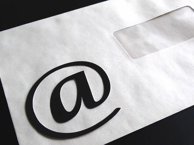 Un sobre blanco de correspondencia con una arroba dibujada