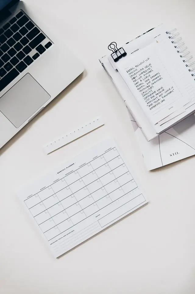 Una laptoo, una libreta y una hoja de calendario