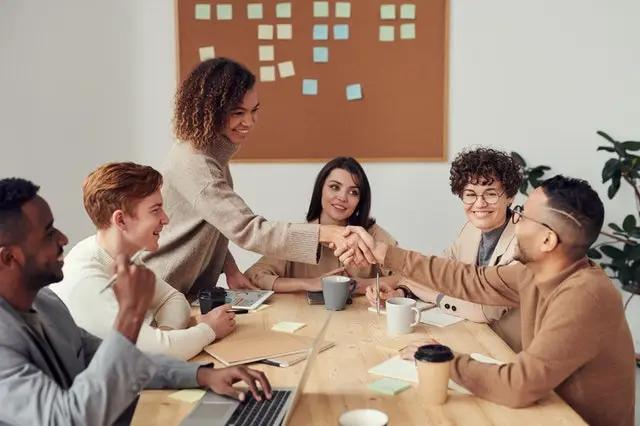 Personas sonrientes se saludan en una reunión de trabajo