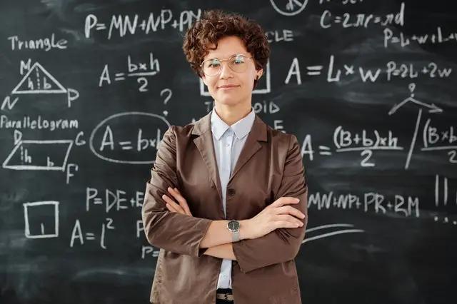 Una maestra y en el fondo una pizarra con fórmulas