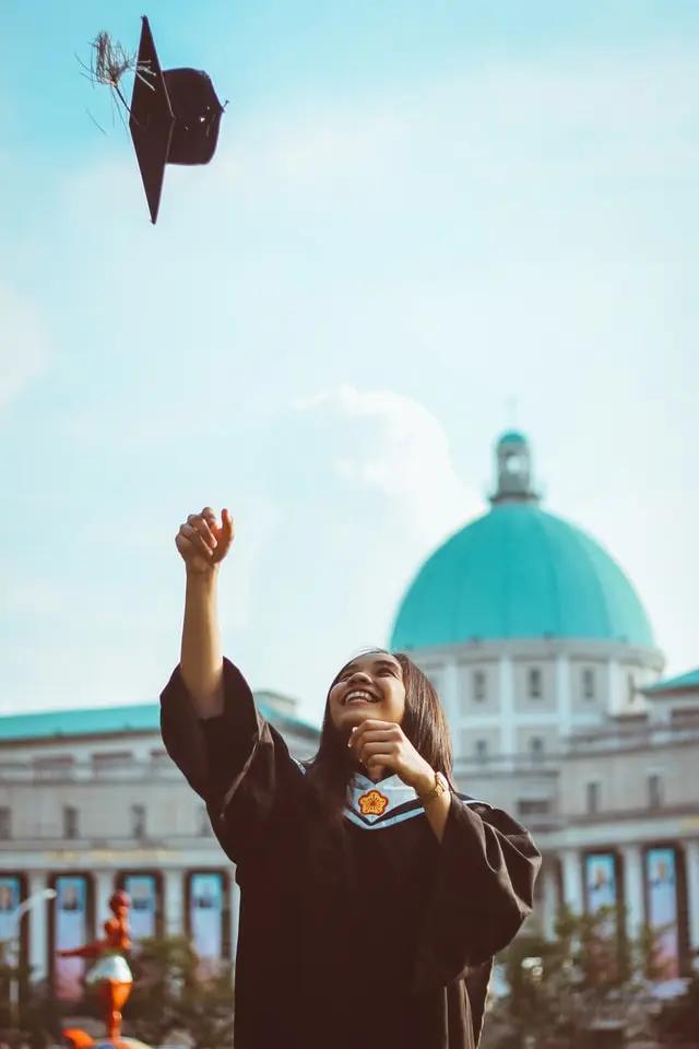 Una chica recién graduada que lanza su birrete hacia arriba