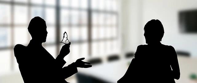Silueta de dos personas sentadas conversando
