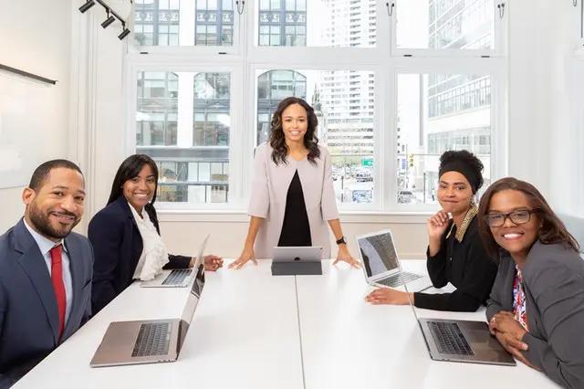 Una jefa sonriente con su equipo de trabajo en una sala de juntas
