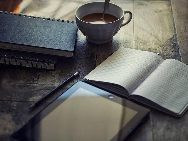 Libretas, tablet y taza de café sobre una mesa de madera