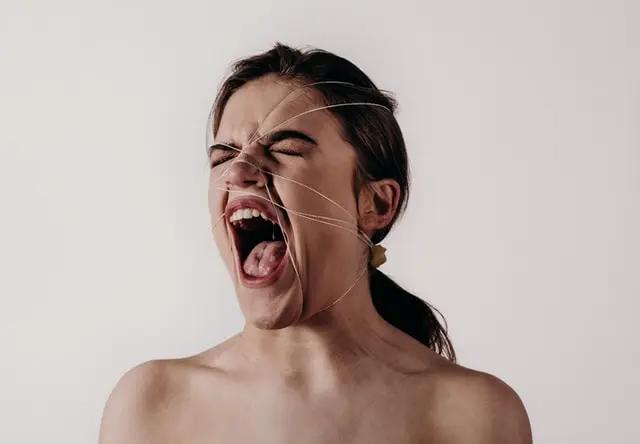 Un mujer gritando con hilos amarrándole la cara