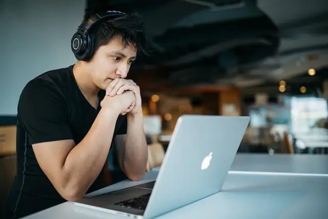 Joven con audífonos frente a una laptop
