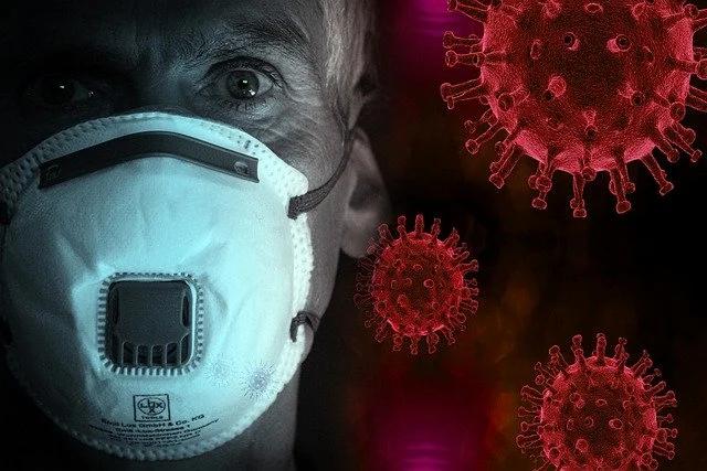 Hombre usando cubrebocas rodeado de virus de COVID-19
